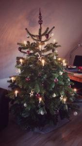 Schöner Weihnachtsbaum geschmückt mit Weihnachtskugeln, Lichterkette und Weihnachtsdeko.