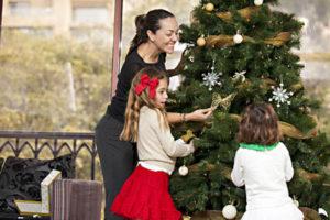 Familie schmückt den Weihnachtsbaum festlich